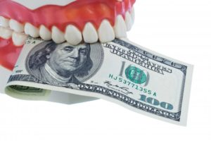 A denture holding a one hundred dollar bill.