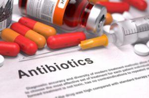 antibiotics description sitting underneath pills and a syringe