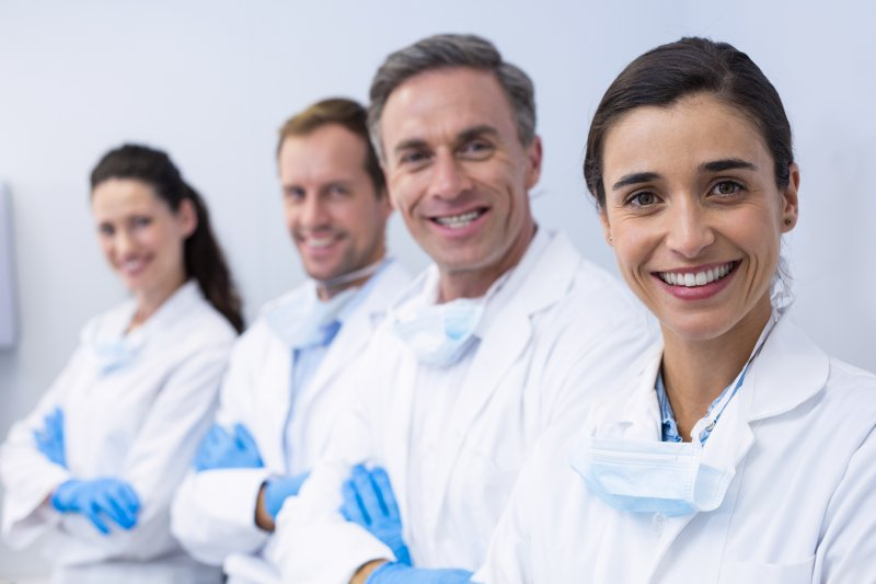 a team of both men and women dental professionals in a line and smiling
