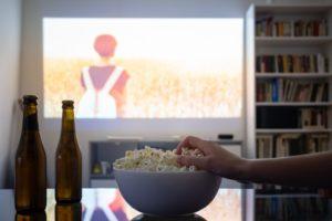 person eating popcorn while binge-watching tv in deer park